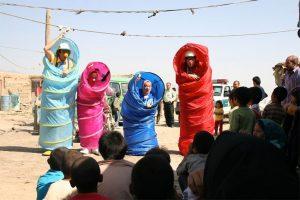 Vier Clowns schauen aus Zelttuch-Röhren ins Publikum