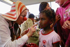 Clownin malt Mädchen roten Fleck auf die Nase