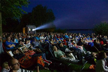 Filmpublikum abends mit Vorführhäuschen, im Hintergrund der See